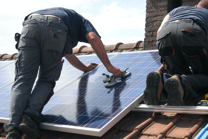 Engineer installing solar panels on roof for net-zero targets.
